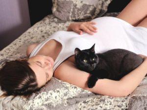 беременная женщина лежит с кошкой
