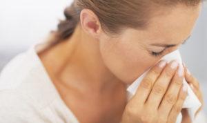 женщина чихает из-за аллергии на кошек